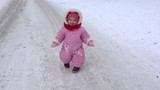 Little baby girl with mother walk on winter snowy road in park. 4K