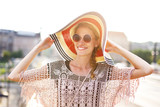Trendy woman in hat and glasses portrait in city