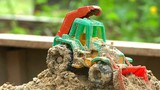 Toy tractor in the sandbox slow motion video