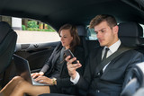 Fototapety Young Businessman And Businesswoman Traveling In The Car