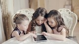 Girls watching photos in the tablet and wonder