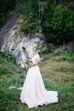 Blonde bride in magnificent long dress poses before the rock