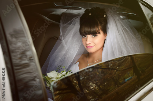 Bride looks out of the white limousine window Poster