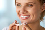 Fototapety Smiling Woman With White Teeth Holding Teeth Whitening Tray. High Resolution Image