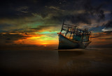 old abandoned boat on the shore under twilight which illuminates him hull and a dramatic cloudy sky