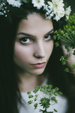 Outdoor artistic portrait of beautiful young woman in a white dress wearing floral wreath.