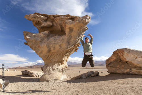 Poster Young man jumping near the Stone tree, Bolivia ( Árbol de Piedra) Isolated rock in the desert
