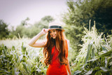 """red-haired girl with freckles in red dress walking on a field of corn she is smiling a 118570515,Sunlight photography with defocused technique"""""""