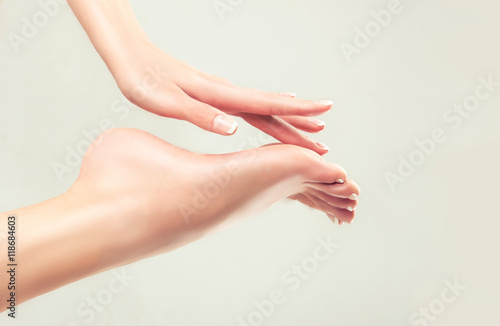 Perfect clean female feet . Beautiful women's hand touches her well-groomed feet. Spa ,scrub and foot care .
