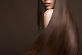 Piękna brunetka z idealnie gładkimi włosami i klasycznym makijażem
