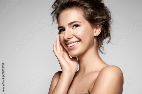 Beautiful smiling girl with clean skin, natural make-up, and white teeth on grey background