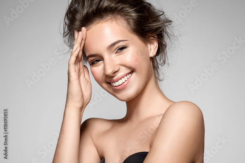Portrait of a smiling young pretty woman with natural make-up and clean skin Poster