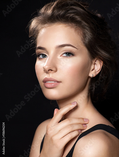 Plakat Close up woman face with beautiful eyes and perfect skin on black background