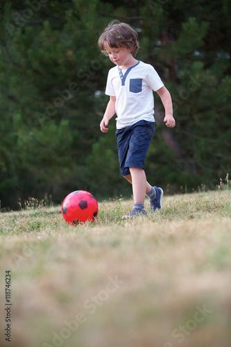 Junge mit einem Fußball im Sommer