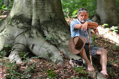 Mann macht eine Wanderpause auf Wurzel Poster