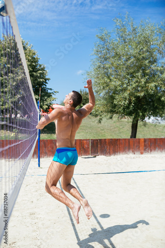 Beach volleyball - Young handsome man playing beach volleyball Poster