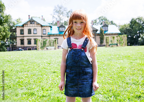 Zdjęcia na płótnie, fototapety, obrazy : Cute little girl standing against a green lawn and big village house and smiling