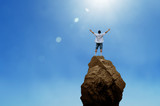 Cheering man open arms on mountain peak cliff