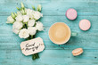 Coffee mug with macaron, white flowers and notes good morning on blue rustic table from above. Beautiful breakfast. Flat lay.