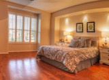 Irvine, CA, USA – August 19, 2016: Large master bedroom with recessed lighting, wood floors and feng shui decor. The bed has a tan pattern duvet comforter with fluffy pillows.