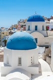 White and blue view of Santorini with two domes