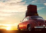 Retro czerwony samochód z bagażem na stojaku na dachu o zachodzie słońca. Podróże, koncepcje wakacyjne.