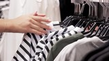 Clothes hanging on rack and female hand