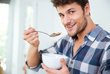 Happy young man eating cereals with milk at home