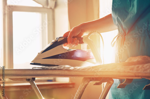 woman ironing clothes on ironing board Poster
