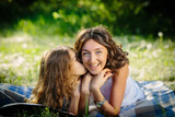 Happy daughter kiss her mother lying outdoors smiling