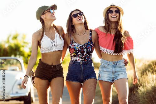 Three beautiful young women enjoying summer on road trip.