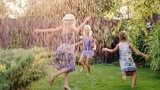 Group of carefree cheerful children playing in the garden. Running around barefoot on the grass under the jets of water or rain.