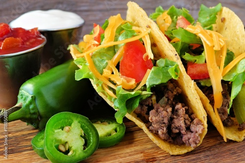 Hard shelled tacos with ground beef, lettuce, tomatoes and cheese close up, on r Plakát