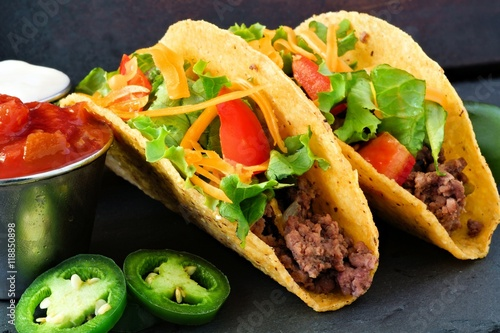 Vászonkép Hard shelled tacos with ground beef, lettuce, tomatoes and cheese close up, on s