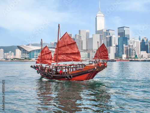 Poster Hong Kong traditional red-sail Junk boat on city skyscrapers background