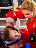 Close up of two aggressive boxer women wearing boxer red gloves boxing in ring. Blonde and brunette on boxing ring.