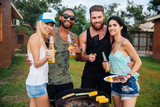 Group of happy friends drinking beer and having barbecue outdoors