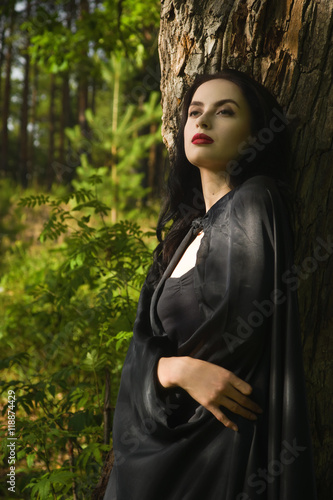 Poster Beautiful brunette woman in black dress and black cloak in the m