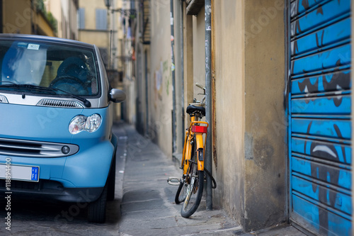 Fototapeta Orange bicycle and blue car on the street in Italy