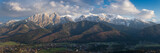 Panorama of snow-capped High Tatras on the Polish side, with a beautiful cloudy sky and a view of the city of Zakopane with many interesting details
