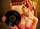 Girl in pin-up style holding vinyl record. Pin-up retro female style.