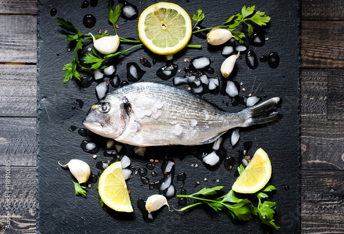 Poster Fresh Fish Orata Over a Black stone with vegetables
