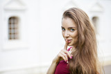 Young beautiful brunette woman has put forefinger to lips as sig