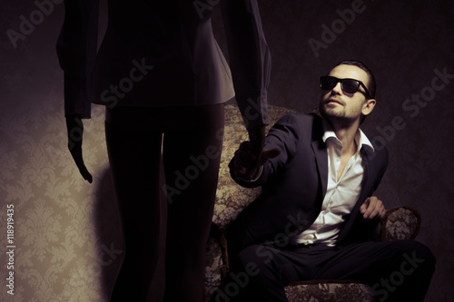 Young and elegant man sitting in chair looking at woman standing in front of him isolated over vintage background Poster