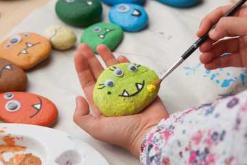 Child painting a stone monster craft © Saltodemata