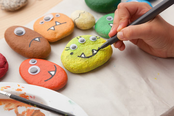 Child painting a stone monster craft © Saltodemata