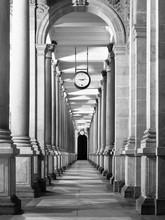 Long couloir colonnafe avec des colonnes et de l'horloge suspendus au plafond. perspective Cloître. . Image en noir et blanc.