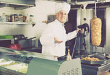 man chef wearing uniform cutting meat for kebab on kitchen in fa