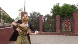 Couple of young man and woman dancing in historical costumes in the street. 4K