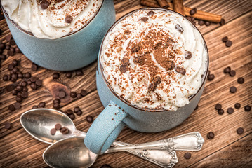 Hot chocolate with whipped cream in mug on a wooden table.